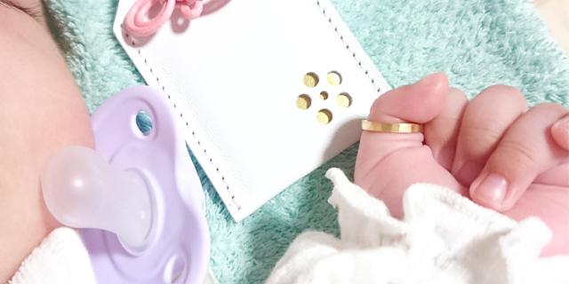 赤ちゃんの親指につけられたベビーリング